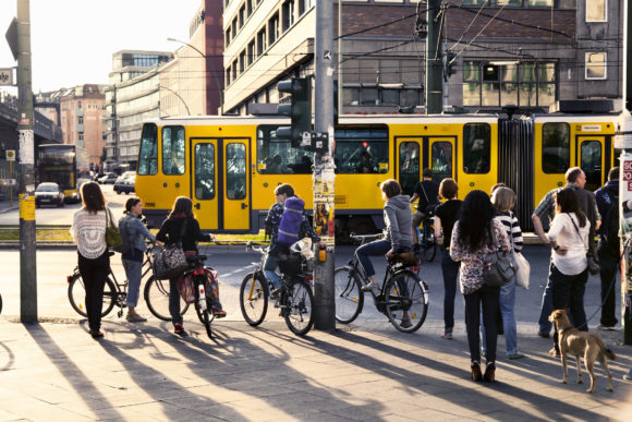 Berlin, Germany - June 12th, 2012: A group of people waiting on the pavement by the crosswalk for the tram to pass and a green light. Early summer evening at Alexanderplatz.