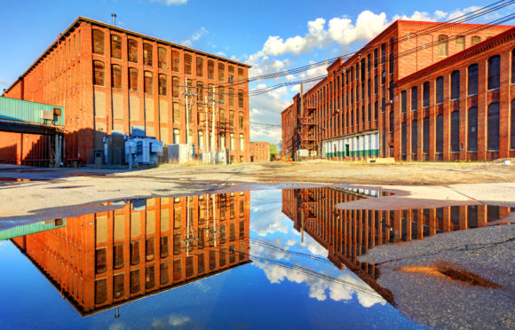 Mill buildings reflecting on puddle in Lawrence, Massachusetts.  Lawrence is a city in Essex County, Massachusetts, United States, on the Merrimack River.